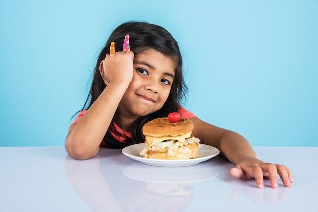 Schattig indiaas of aziatisch meisje dat smakelijke hamburger, sandwich of pizza eet in een bord of doos. staande geïsoleerd over blauwe of gele achtergrond.