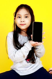 Schattig jong aziatisch meisje, mooie glimlach en blij om het scherm van de smartphone te tonen om aan te kondigen, een significant promotiebericht uit te drukken voor interessante technologiecommunicatie en contactgegevens uit te leggen