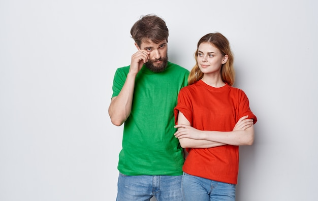 Schattig jong koppel in veelkleurige t-shirts hugs levensstijl plezier geïsoleerde achtergrond