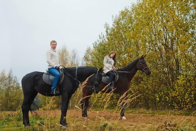 Schattig jong koppel te paard in herfst bos op landweg. renners in de herfst parkeer bij guur bewolkt weer met lichte regen