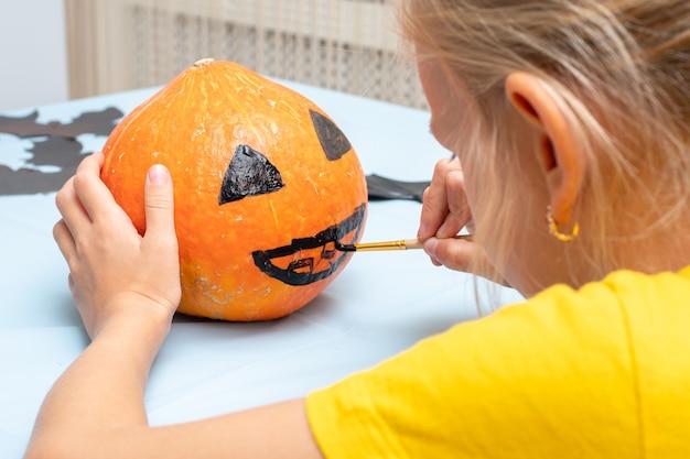 Schattig jong meisje dat eng gezicht op oranje pompoen schildert met borstel voor huisdecoratie tijdens halloween-vakantie, achteraanzicht, close-up. achtergrond voor halloween-feest en familielevensstijl