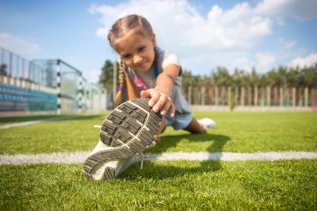 Schattig jong meisje dat zich uitstrekt op gras voordat ze gaat rennen