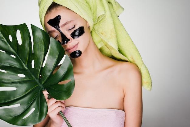 Schattig jong meisje met een groene handdoek op haar hoofd, op haar gezicht een zwart masker tegen acne