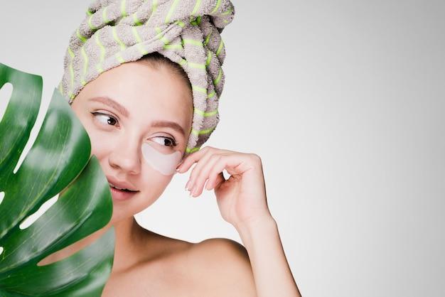 Schattig jong meisje met een handdoek op haar hoofd genietend van een spa, onder de ogen patches