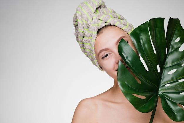 Schattig jong meisje met een handdoek op haar hoofd houdt een groen blad vast, geniet van een spa