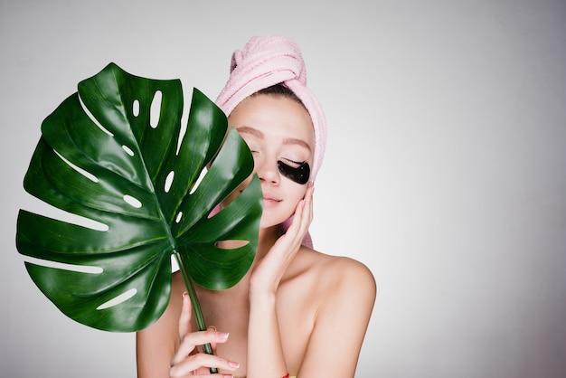 Schattig jong meisje met een roze handdoek op haar hoofd genietend van de spa, onder de ogen van zwarte vlekken, haar ogen zijn gesloten