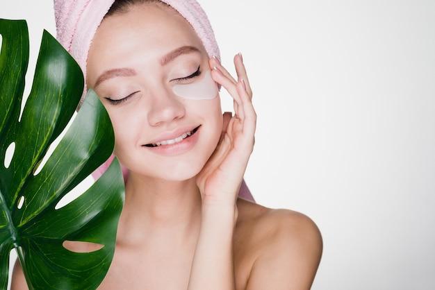 Schattig jong meisje met een roze handdoek op haar hoofd genietend van een spa, onder de ogen patches