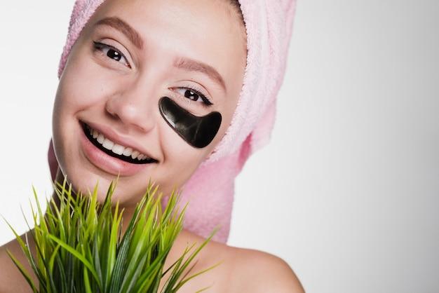 Schattig jong meisje met een roze handdoek op haar hoofd glimlachend, houd een groene plant vast