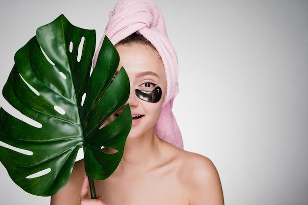 Schattig jong meisje met een roze handdoek op haar hoofd, houdt een groen blad vast, onder haar ogen zwarte vlekken, dag spa