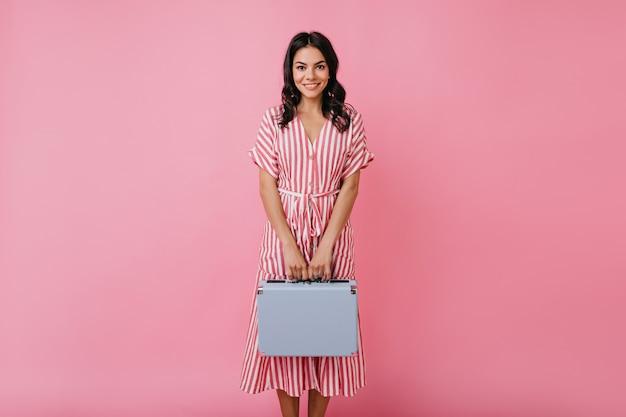 Schattig jong meisje met lang donker haar in roze jurk bescheiden poseren met blauwe koffer, op zoek met vriendelijke glimlach.