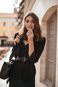 Schattig jong meisje met medium golvend kapsel, moderne make-up, groene zijden jurk, zwarte jas en stijlvolle accessoires poseren op daglicht straat en kijken naar voren
