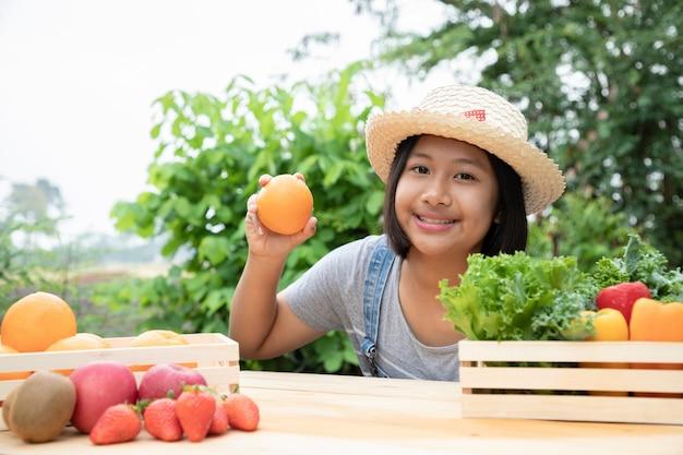 Schattig jong meisje plukken een sinaasappelen in houten kist uit de tuin. ze houdt van tuinieren en verkopen van producten. concepten van landbouw en niet-giftig fruit. zachte focus. tuin en boerderij concept.