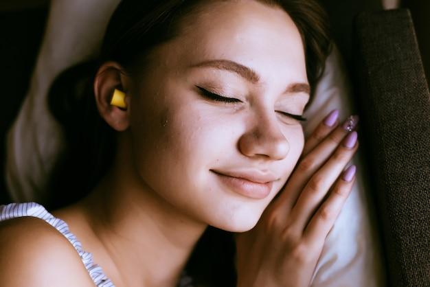 Schattig jong meisje slapen, in de oren gele oordopjes tegen straatlawaai