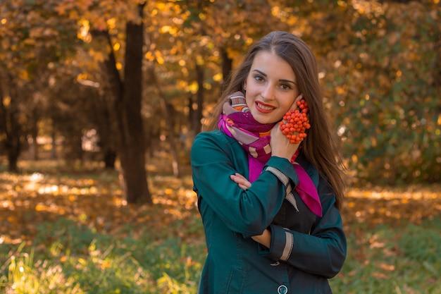 Schattig jong meisje staat in het herfstpark met een takje rowan in haar hand