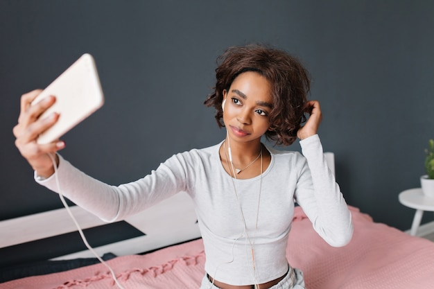 Schattig jong meisje, tiener nemen selfie, luisteren naar muziek op bed met roze tapijt in kamer met grijze muur. het dragen van een lichtgrijs t-shirt met lange mouwen, hangende driehoek.