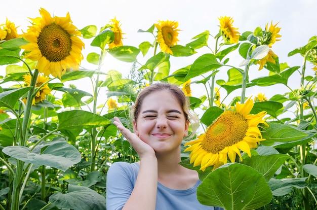 Schattig jong meisje tussen zonnebloemen