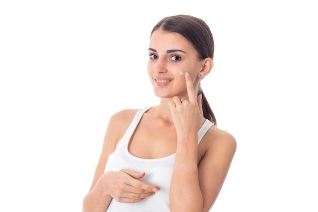 Schattig jong meisje zorgt voor haar huid met crème geïsoleerd op een witte achtergrond. gezondheidszorgconcept. lichaamsverzorgingsconcept. jonge vrouw met een gezonde huid.
