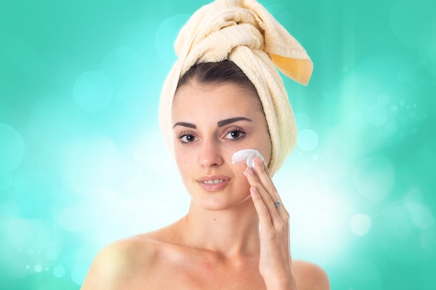 Schattig jong meisje zorgt voor haar huid met handdoek op hoofd besmeurd met crème geïsoleerd op een witte achtergrond. gezondheidszorgconcept. lichaamsverzorgingsconcept. jonge vrouw met een gezonde huid.