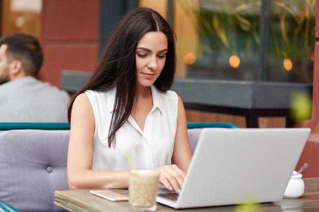 Schattig jong vrouwelijk model typt iets op laptopcomputer, bereidt bedrijfsrepot voor. mooie brunette student bereidt zich voor op eindexamen of werkt op diplomapapier in coffeeshop.