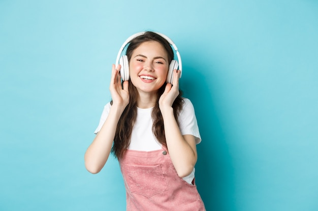 Schattig kaukasisch meisje in lente outfit, muziek luisteren in koptelefoon, tevreden glimlachend in de camera, staande over blauwe achtergrond.