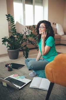 Schattig kaukasisch meisje met bril en krullend haar praten over de telefoon zittend op de vloer en met online lessen