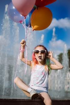 Schattig kaukasisch meisje met kleurrijk geverfd haar met een zonnebril van moeders met ballonnen in de buurt van fo
