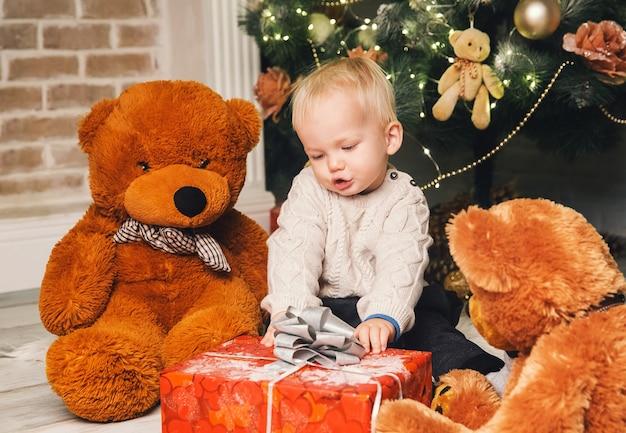 Schattig kind brengt tijd door met familie thuis interieur op de achtergrond van de kerstboom. kleine jongen jongen vieren kerstmis en nieuwjaar.