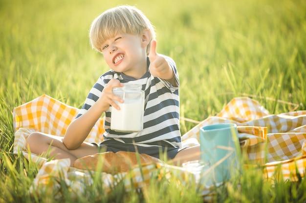 Schattig kind consumptiemelk. aanbiddelijke jongen die brood eet