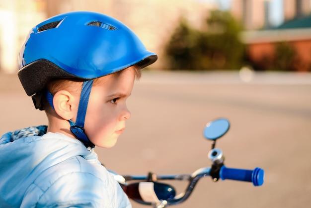 Schattig kind in helm leert en fietst op een zonnige dag bij zonsondergang