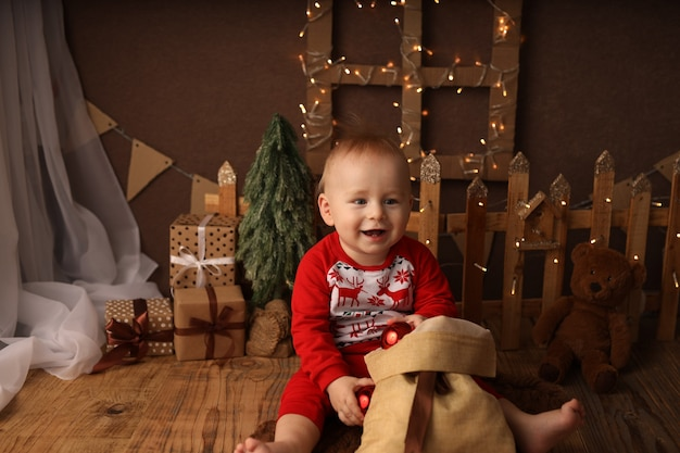 Schattig kind in nieuwjaarspyjama haalt kerstballen uit een tas met cadeaus