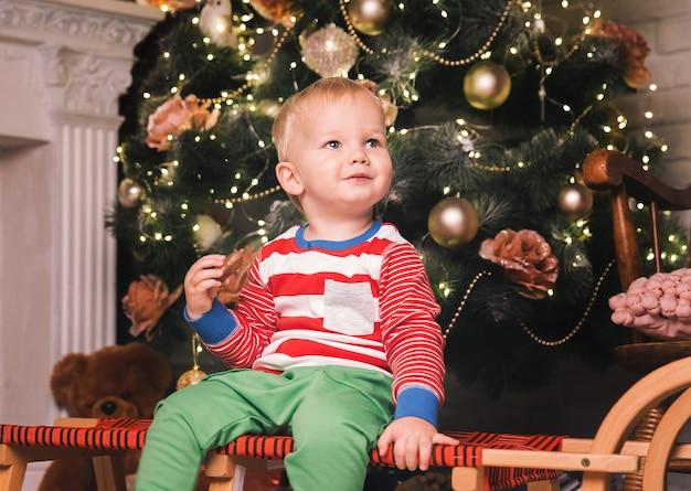 Schattig kind in pyjama tijd doorbrengen met familie thuis interieur op de achtergrond van de kerstboom