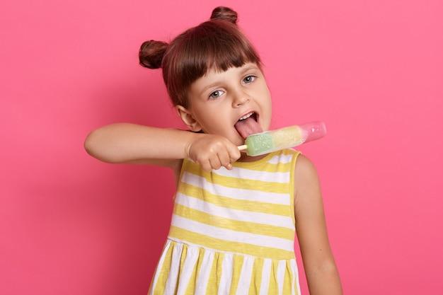 Schattig kind meisje houdt ijs in de hand en houdt de mond geopend, likken sorbet, grappige peuter kind poseren geïsoleerd op roze achtergrond, charmante kleine dame met knopen.