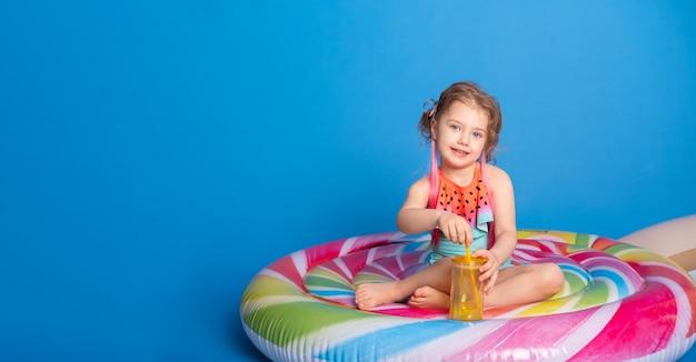 Schattig kind meisje in zwempak drinken sinaasappelsap zittend op kleurrijke opblaasbare matras op bl...