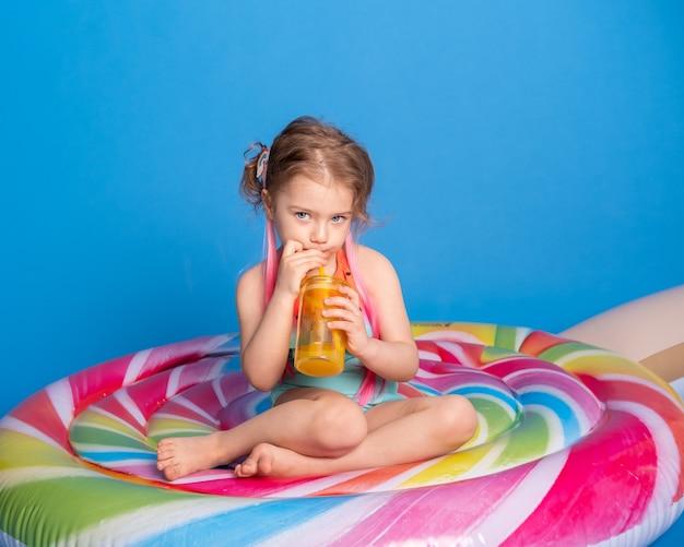Schattig kind meisje in zwempak drinken sinaasappelsap zittend op kleurrijke opblaasbare matras.