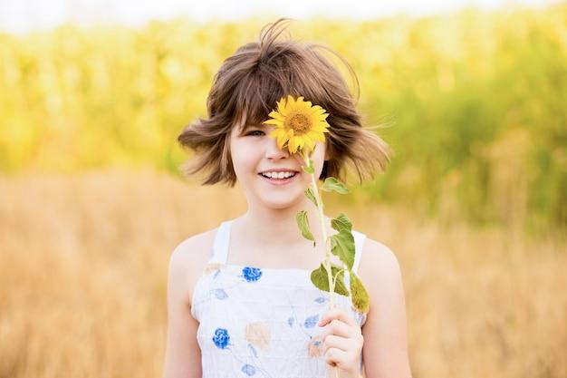 Schattig kind meisje met zonnebloem in lente veld gelukkig klein meisje verbergt oog met zonnebloem