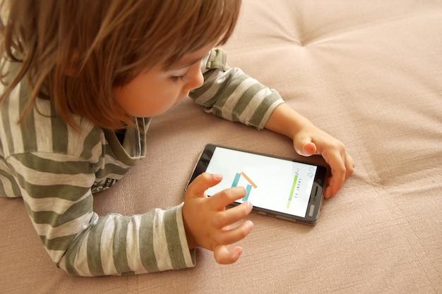 Schattig kind meisje spelen spel op slimme telefoon