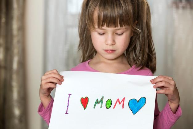 Schattig kind meisje wit vel papier met kleurrijke kleurpotloden geschilderde woorden ik hou van moeder. kunstonderwijs, creativiteit concept.