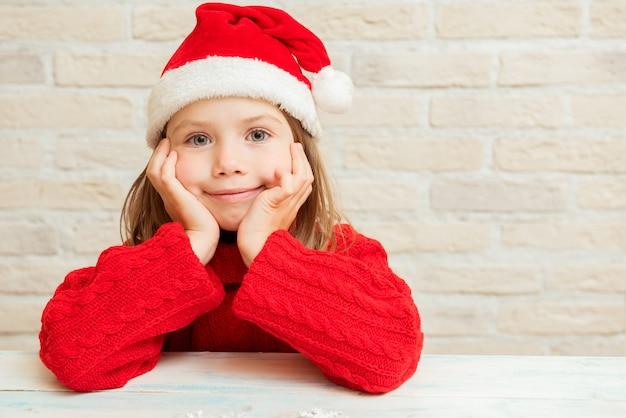 Schattig kind meisje zit in de rode hoed van de kerstman te wachten op de vakantie, kerstmis, nieuwjaar
