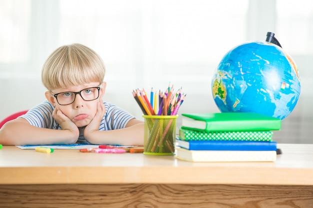 Schattig kind saai op de les. het kind wil geen huiswerk of klaswerk maken. ongelukkige schooljongen.