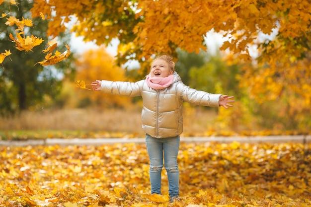 Schattig kind spelen met herfstbladeren