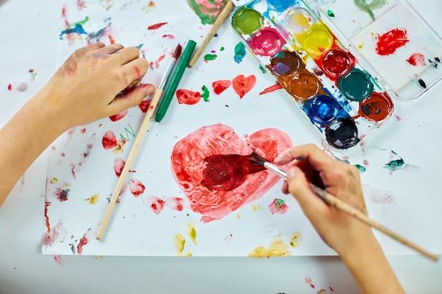 Schattig kind zit aan tafel en tekent rood hart op wit papier, art school concept, meisje kind schilderen met aquarel verf thuis