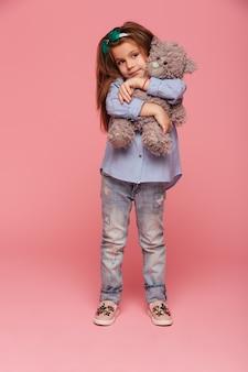 Schattig kindmeisje met lang kastanjebruin haar en vrijetijdskleding die haar mooie teddybeer knuffelen