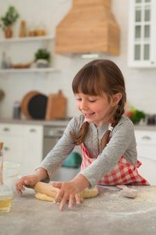Schattig klein 4-jarig meisje met staartjes rolt deeg uit met een deegroller op de keukentafel.