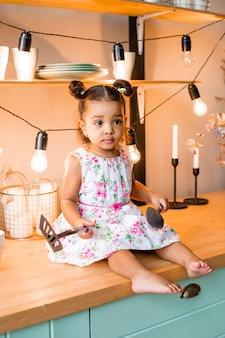 Schattig klein afrikaans amerikaans meisje thuis in de keuken