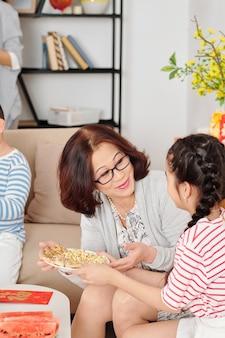 Schattig klein aziatisch meisje dat bord met zelfgemaakte koekjes geeft aan haar gelukkige grootmoeder als ze in de woonkamer zitten, kaarten met de beste wensen op tafel