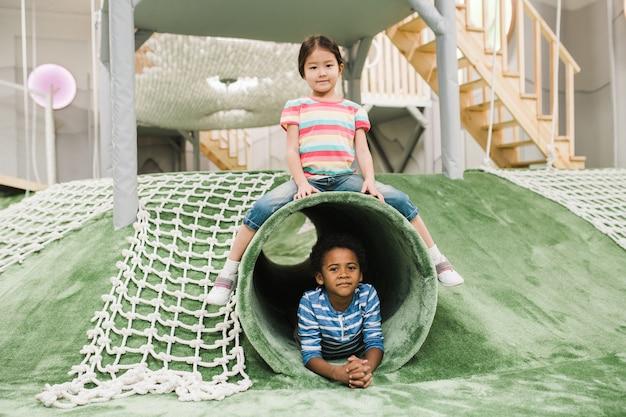 Schattig klein aziatisch meisje en haar vriend van afrikaanse afkomst met plezier op speelplaats in modern recreatiecentrum