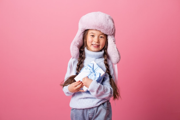 Schattig klein aziatisch meisje in een muts en trui houdt een geschenkdoos. kerst concept, tekst ruimte