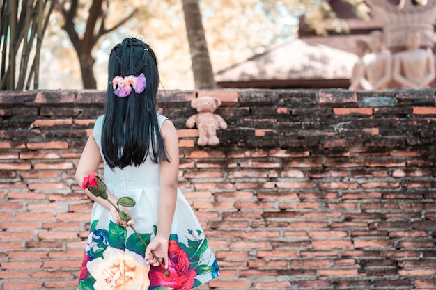 Schattig klein aziatisch meisje in jurk staan achterover en houden een rode roos geven aan een beer in het park