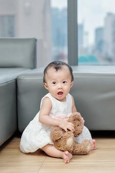 Schattig klein aziatisch meisje in mooie jurk zittend op de vloer met teddybeer