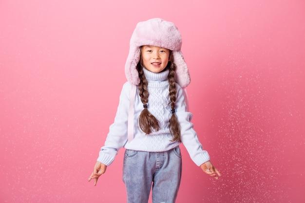 Schattig klein aziatisch meisje in winterkleren blaast sneeuw uit palmen. winter einde, roze achtergrond, ruimte voor tekst